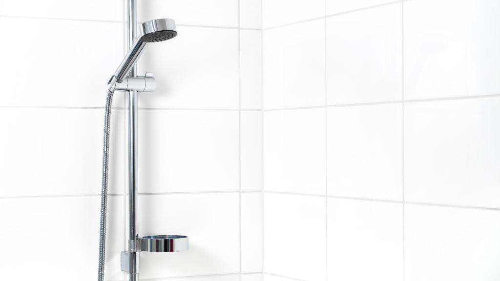 Shower hose on the wall of a bathroom with white tiles