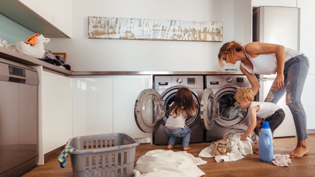 Woman and two toddlers doing laundry together