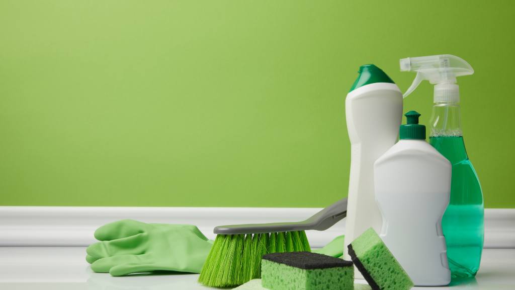 Cleaning products without labels in front of a green wall