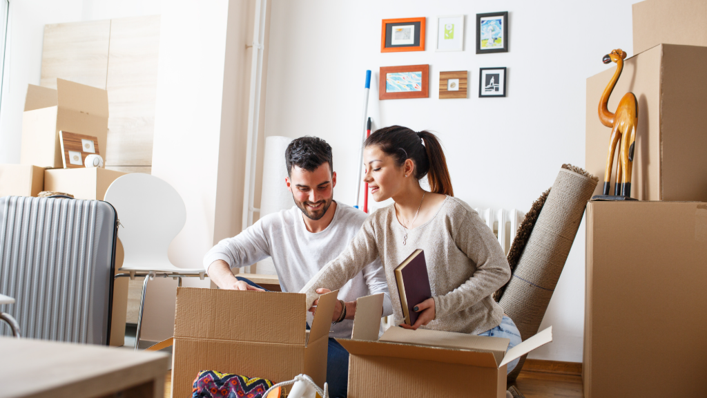 Couple packing things into cardboard boxes at home.