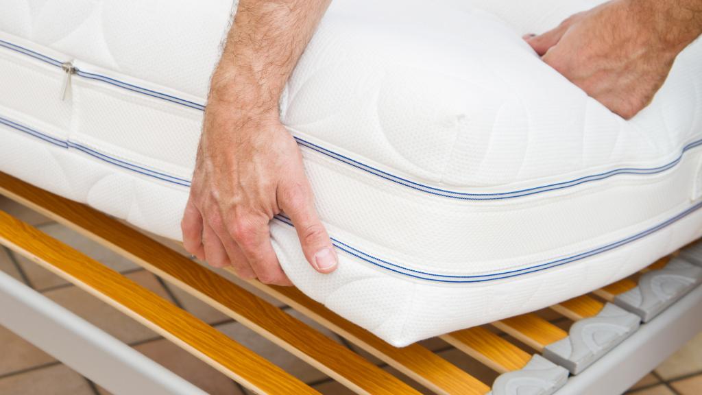 A man fixing the mattress.